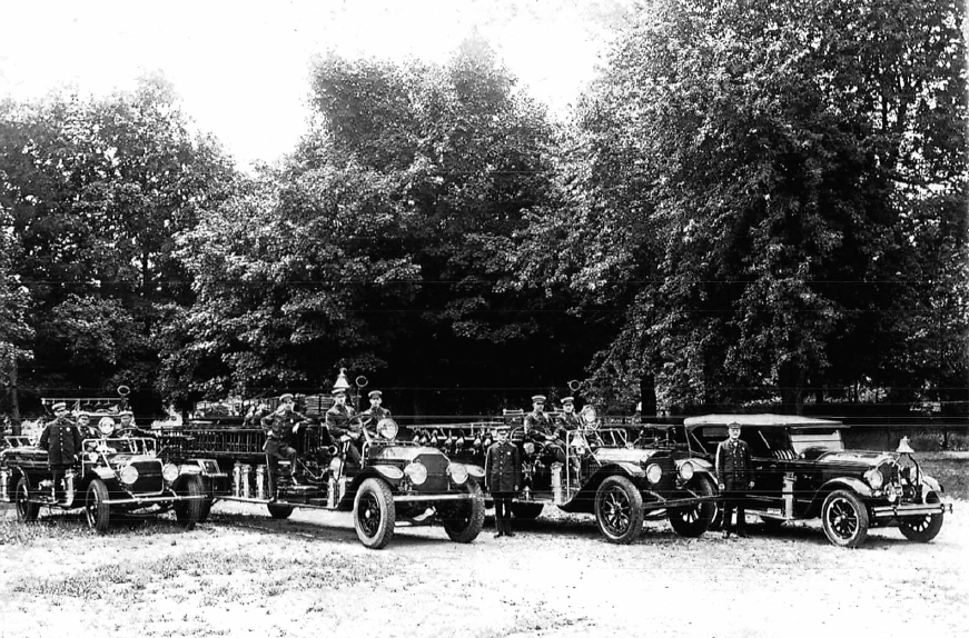 P15 The Needham Fleet c1930 Dick Salamone on running board far left, 3rd truck from left Walter Mullin, Leo Brady.png